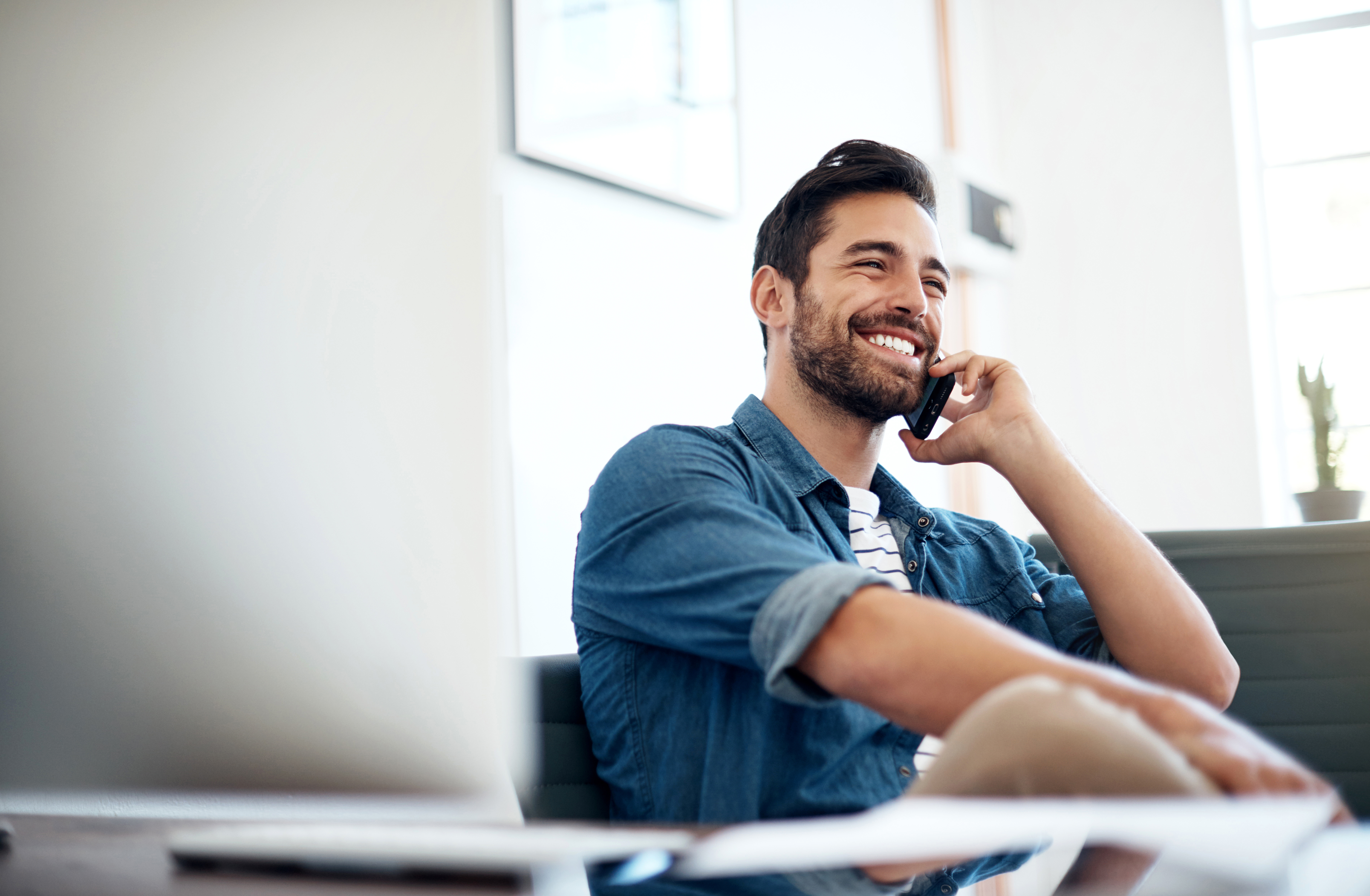 Man sitting and smiling while talking on his phone